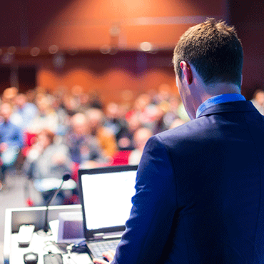 viewer standing behind person seated at podium with audience out of focus in background