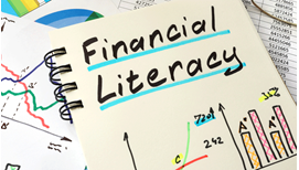written in ink, the words 'financial literacy' on a sheet among charts and spread sheets