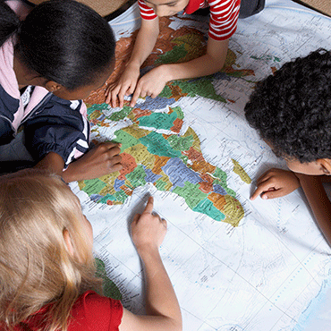 diverse children around global map pointing